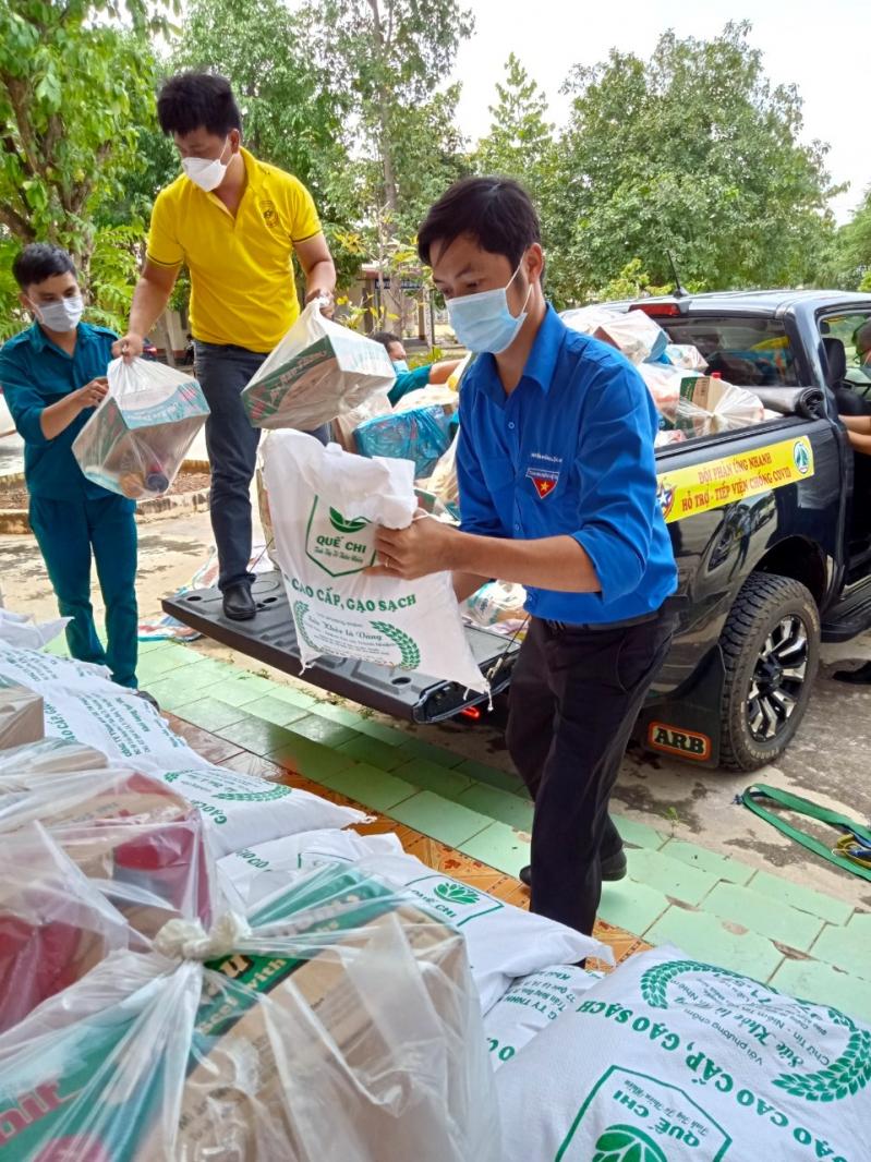 Thanh niên huyện biên giới Lộc Ninh cùng các thành viên đội phản ứng nhanh Sao Nhân Ái hăng hái khuân vác nhu yếu phẩm xuống xe.
