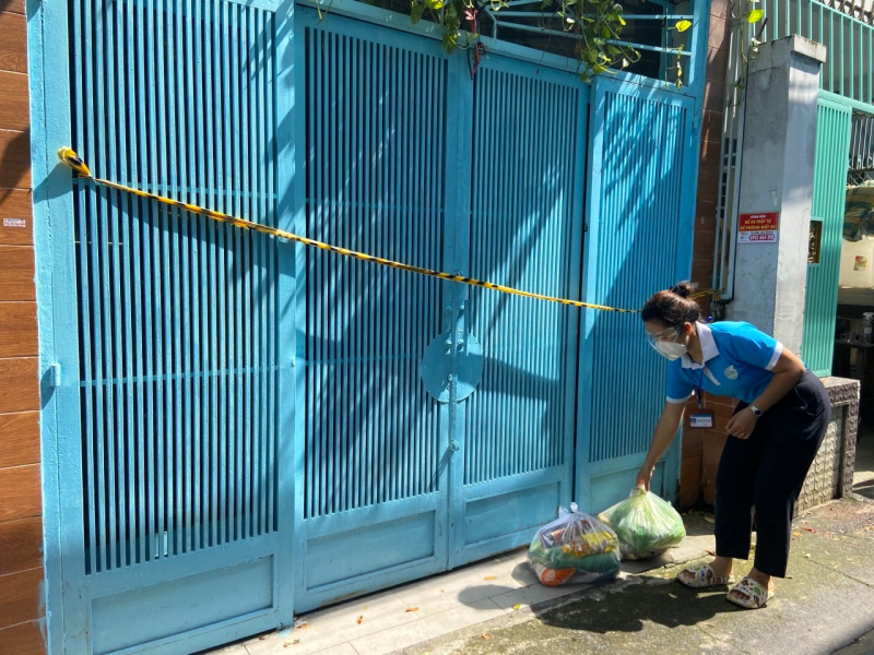 Một tình nguyện viên đặt chiếc túi an sinh thắm tình người Bình Phước trước nhà của một hộ dân P.10, Quận Tân Bình để người nhà ra lấy ngay sau đó.