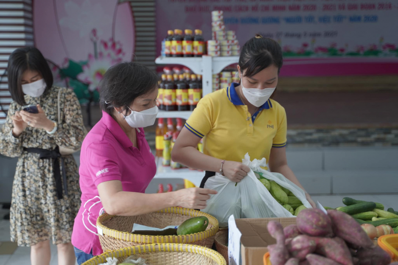 Bà Dung hướng dẫn các tình nguyện viên châm hàng tươi mới vào siêu thị mini 0 đồng. Ảnh: PNJ