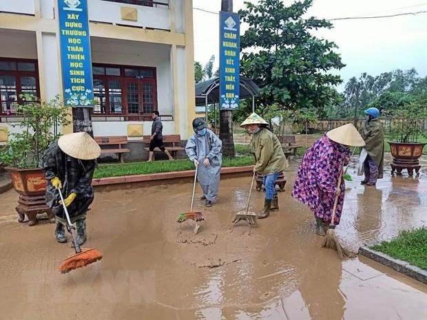 Người dân dọn dẹp vệ sinh sau mưa lũ. Ảnh: TTX